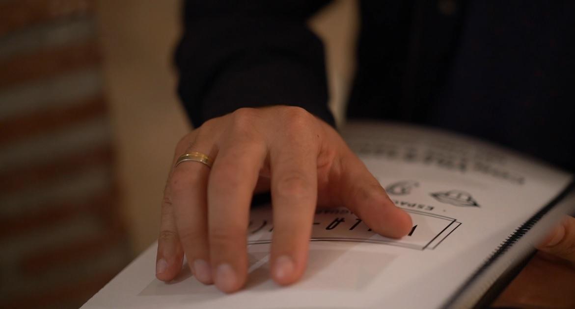 Persona ciega leyendo el catálogo accesible de Villa Lucía en braille