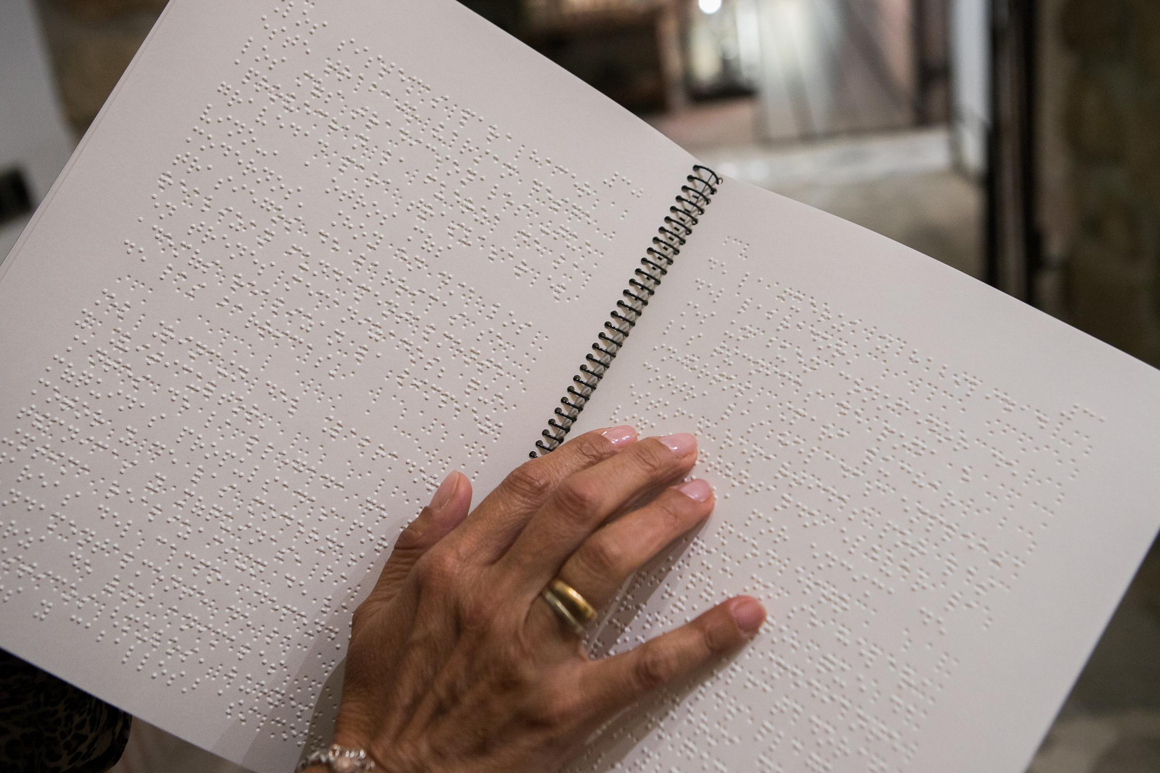 Persona ciega leyendo libro en braille. Proyecto de accesiblidad desarrollado por Equalitas Accesibilidad